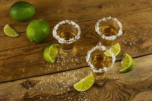 Tequila shots with lime and salt on the wooden surface top view