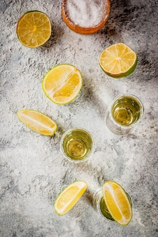 Tequila shots with lime and sea salt on grey stone table,  top view