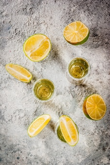 Tequila shots with lime and sea salt on grey stone table top view