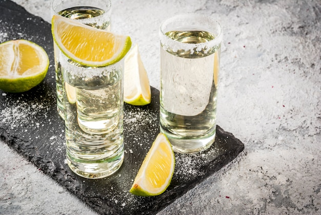 Tequila shots with lime and sea salt on grey stone table