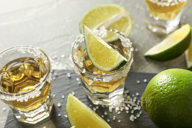 Tequila shots with salt and lime slices on grey