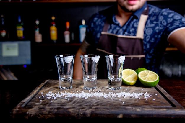 Текила серебряная, спирт в рюмках, лайм и соль, тонированное изображение, выборочный фокус