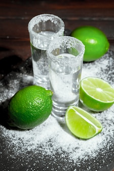 Tequila silver shots with lime slices and salt on wooden board