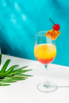 Tequila sunrise cocktail on blue background