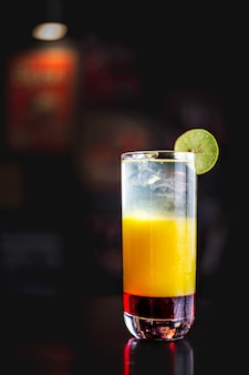Tequila sunrise in a dark ambient bar