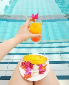 Tequila sunrise or orange juice in female hand served mango tropical flower bougainvillea in pool. lifestyle vocation relax rest spa