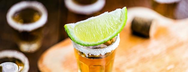 テキーラ、典型的なメキシコの飲み物、レモンに選択的な焦点。国際テキーラデー Premium写真