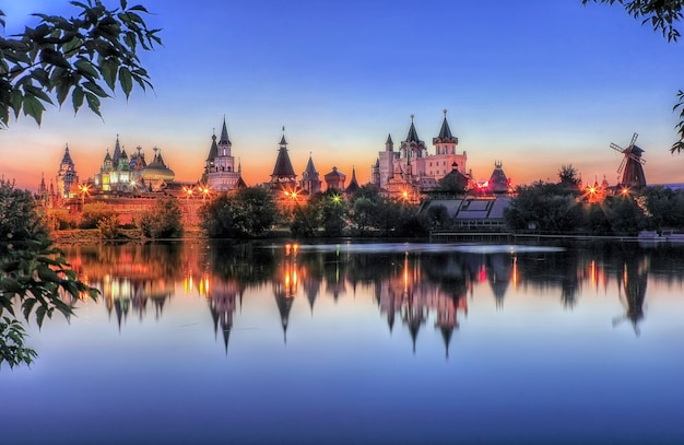 Teremki of the izmailovsky kremlin in moscow with reflection in the water of the pond in the light of evening lights