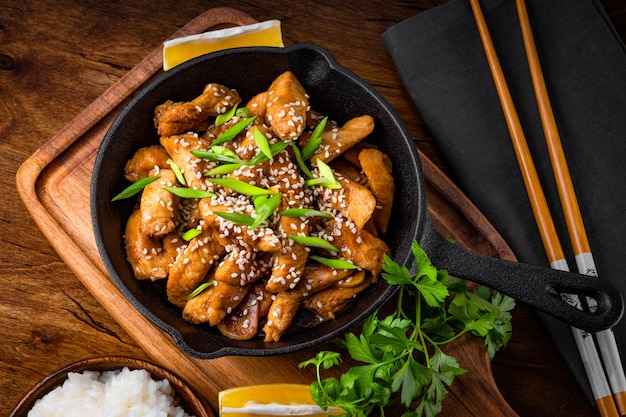 Teriyaki chicken breast in frying pan with rice and sesame seeds top view, traditional asian food. high quality photo