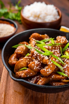 Куриная грудка терияки на сковороде с кунжутом крупным планом, традиционная азиатская еда