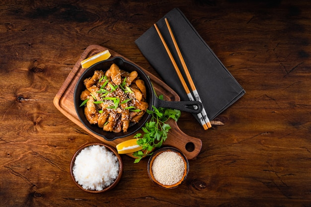 Куриная грудка терияки в сковороде с рисом и семенами кунжута, вид сверху со свободным пространством для текста, традиционная азиатская еда. фото высокого качества
