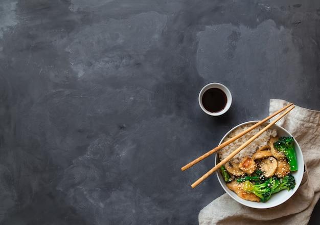 照り焼きチキン、ブロッコリー、マッシュルームは、灰色のコンクリートの背景にボウルに白ご飯と一緒に炒めます。アジア料理。テキスト用のスペースがある上面図。