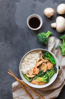 데리야끼 치킨, 브로콜리, 버섯은 회색 콘크리트 위에 그릇에 흰 쌀밥과 함께 볶습니다.