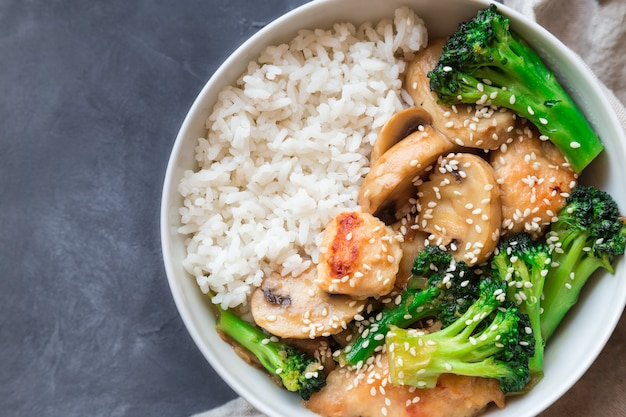 Teriyaki chicken, broccoli and mushrooms stir fry with white rice in bowl on gray concrete background. asian cuisine. top view.