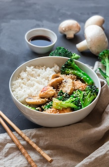 Teriyaki chicken, broccoli and mushrooms stir fry with white rice in bowl on gray concrete table. asian cuisine. selective focus.