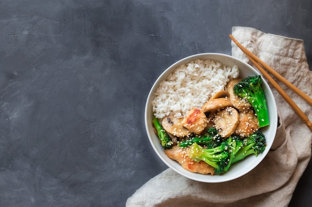 Teriyaki chicken, broccoli and mushrooms stir fry with white rice in bowl on gray concrete