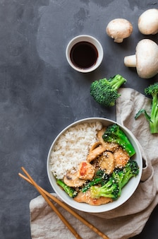 Teriyaki chicken, broccoli and mushrooms stir fry with white rice in bowl on gray concrete.