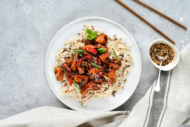 Teriyaki chicken with chili pepper and sesame seeds, with rice.