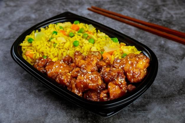 플라스틱 식품 용기에 쌀과 야채를 곁들인 데리야끼 치킨. 일본 요리.