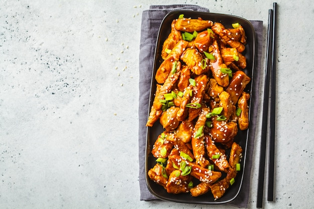 Teriyaki chicken with sesame, green onion in black plate, top view.