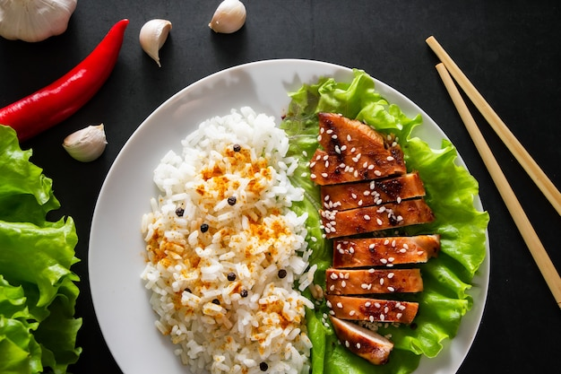 Курица терияки с белым рисом на тарелке. вкусная еда и китайские палочки на темном фоне
