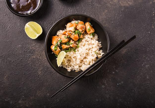 Соус терияки сочные куриные кубики с рисом - вкусный обед в азиатском стиле на фоне темноты, вид сверху