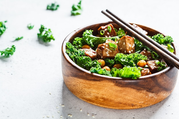 Teriyaki tofu salad with kale and chickpeas in a wooden bowl, copy space.