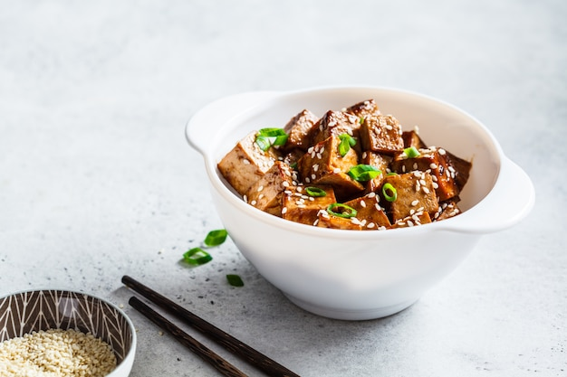 Teriyaki tofu with sesame seeds and green onion in white bowl. vegan food concept.