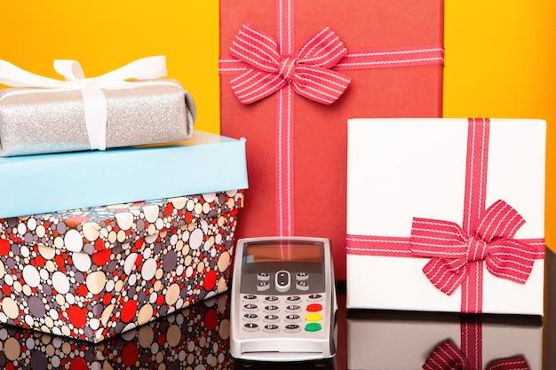 Терминал, коробки с подарками на черном стеклянном столе и желтом фоне. концепция покупок подарков.