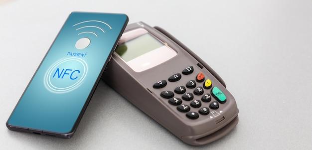Терминал для бесконтактной оплаты со смартфоном на белом фоне