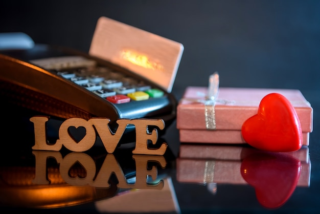 Terminal with credit card and gift box with love text