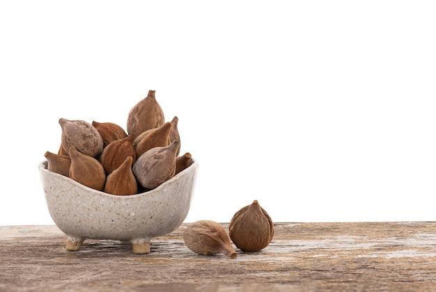 클리핑 패스가 있는 나무 테이블에 있는 그릇에 terminalia bellirica 또는 beleric myrobalan 과일.