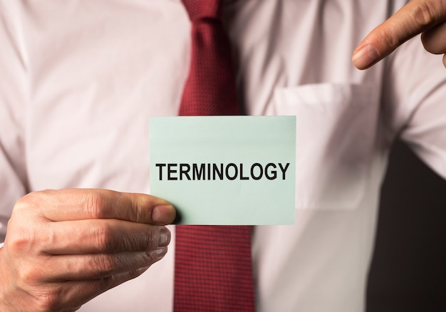 Terminology word on paper note in hands of businessman concept of terms in finance business and acco...