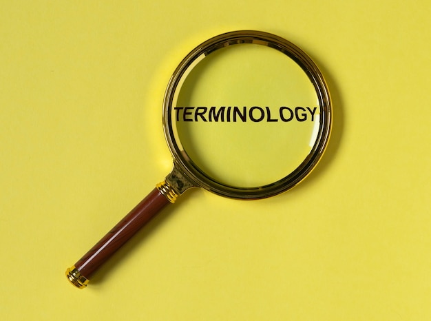 Terminology word through magnifier on bright yellow background top view
