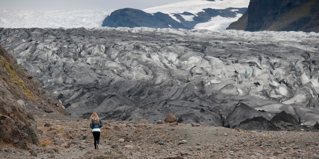 Terminus of glacier with girl to show scale