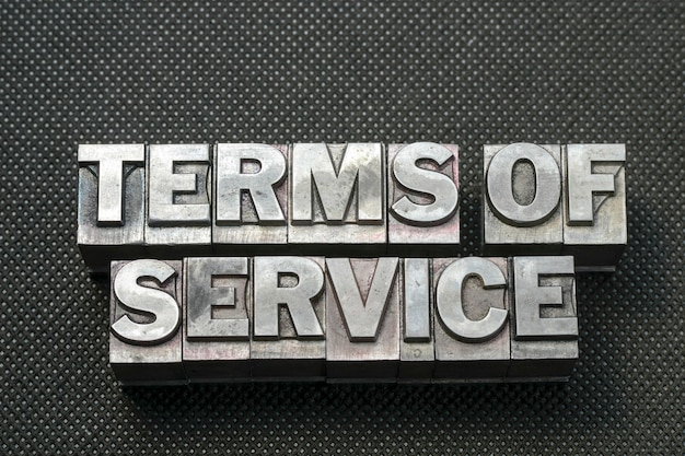 Terms of service phrase made from metallic letterpress blocks on black perforated surface