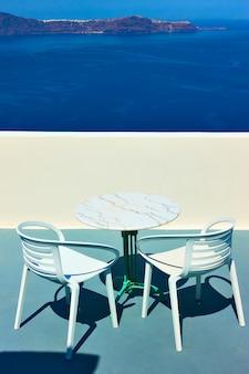 그리스 산토리니 섬에 있는 탁자와 안락의자가 있는 바다 위의 테라스. 그리스 리조트의 모습