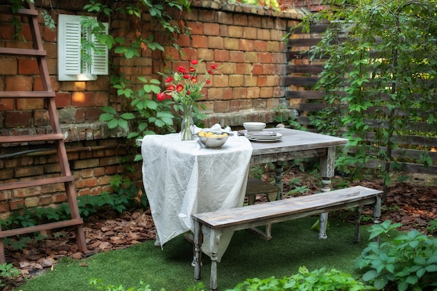 Дом с террасой с кирпичной стеной и растениями, обеденный стол и деревянная скамья в саду с патио