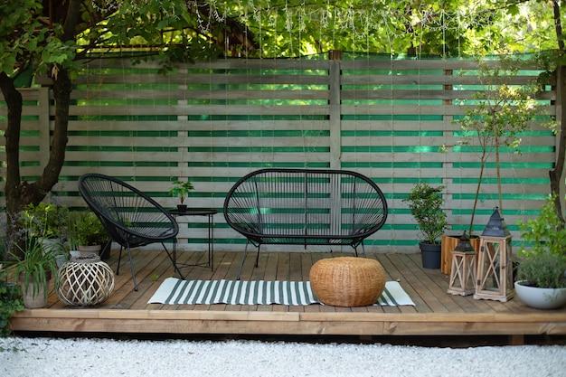 식물 테이블 소파 안락의자와 랜턴이 있는 테라스 하우스 아늑한 파티오 또는 발코니 현대적인 라운지
