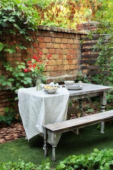 Дом с террасой со столом и деревянной скамейкой сад с патио деревянная садовая мебель