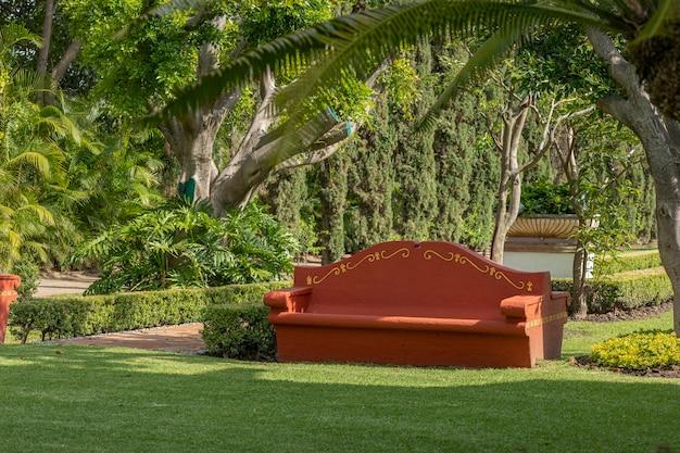 背景と青い空に木があるテラコッタ色のコンクリートベンチ