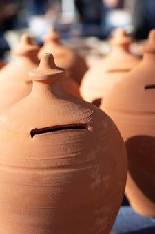 Terracotta money saving box or piggy bank, selective focus