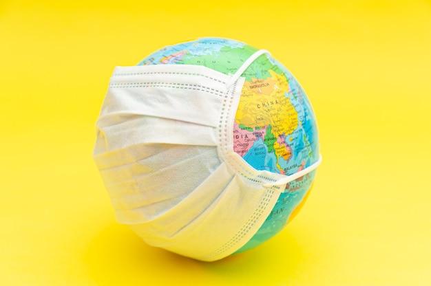 黄色の背景に分離された白いサージカルマスクと地球儀モデル。概念: