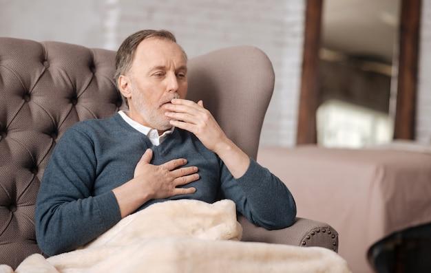 끔찍한 기관지염. 집에서 소파에 앉아있는 동안 선배 잘 생긴 남자가 정말 강하게 기침하고 있습니다.