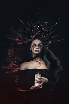 Terrible horror halloween vampire woman portrait. beauty vampire witch lady with blood on mouth posing in deep forest. fashion art design. holds a candle in his hands and reads curses Premium Photo