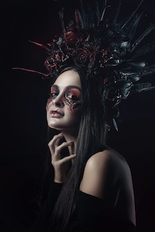 Terrible horror halloween vampire woman portrait. beauty vampire witch lady with blood on mouth posing in deep forest. fashion art design. holds a candle in his hands and reads curses