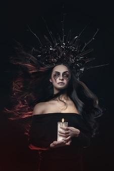 Страшный ужас хэллоуин вампир женский портрет. красавица-вампир-ведьма с кровью во рту позирует в глубоком лесу. модный арт дизайн. держит в руках свечу и читает ругательства
