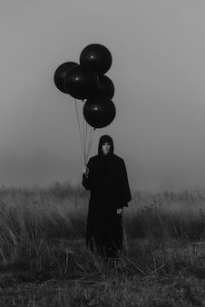 후드가 달린 망토를 입은 끔찍한 남자가 손에 풍선을 들고 안개 낀 들판에 서 있습니다. 신비로운 악몽의 어두운 개념
