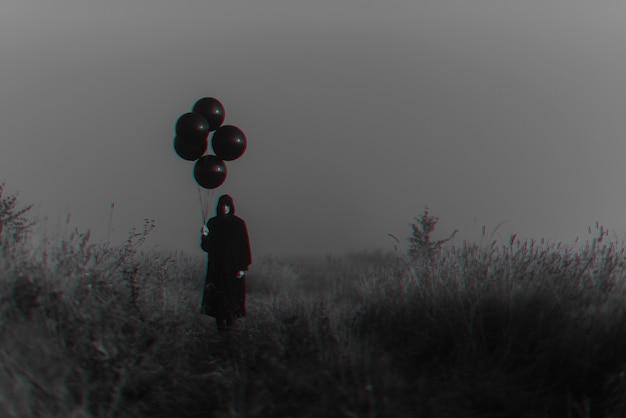 Грозный человек в плаще с капюшоном с воздушными шарами в руке стоит в туманном поле. темная концепция мистических кошмаров