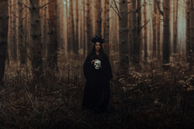 Terrible witch holds the skull of a dead man in her hands in a dark forest